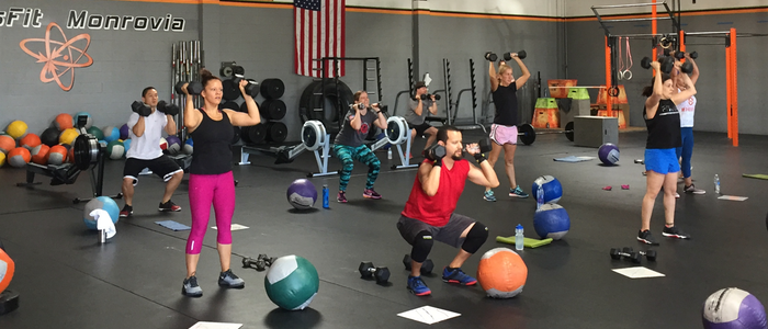 CrossFit Monrovia class using dumbbells to squat and press.
